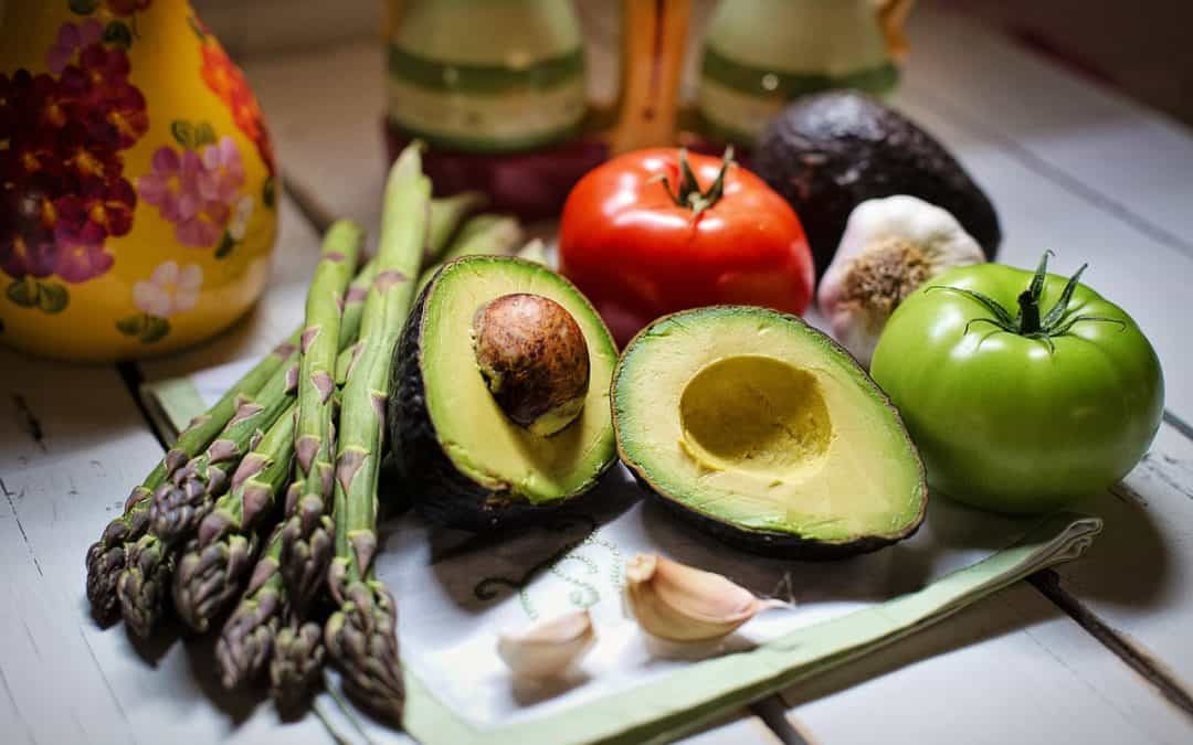A platter of detoxifying foods including avocados, asparagus and tomatoes