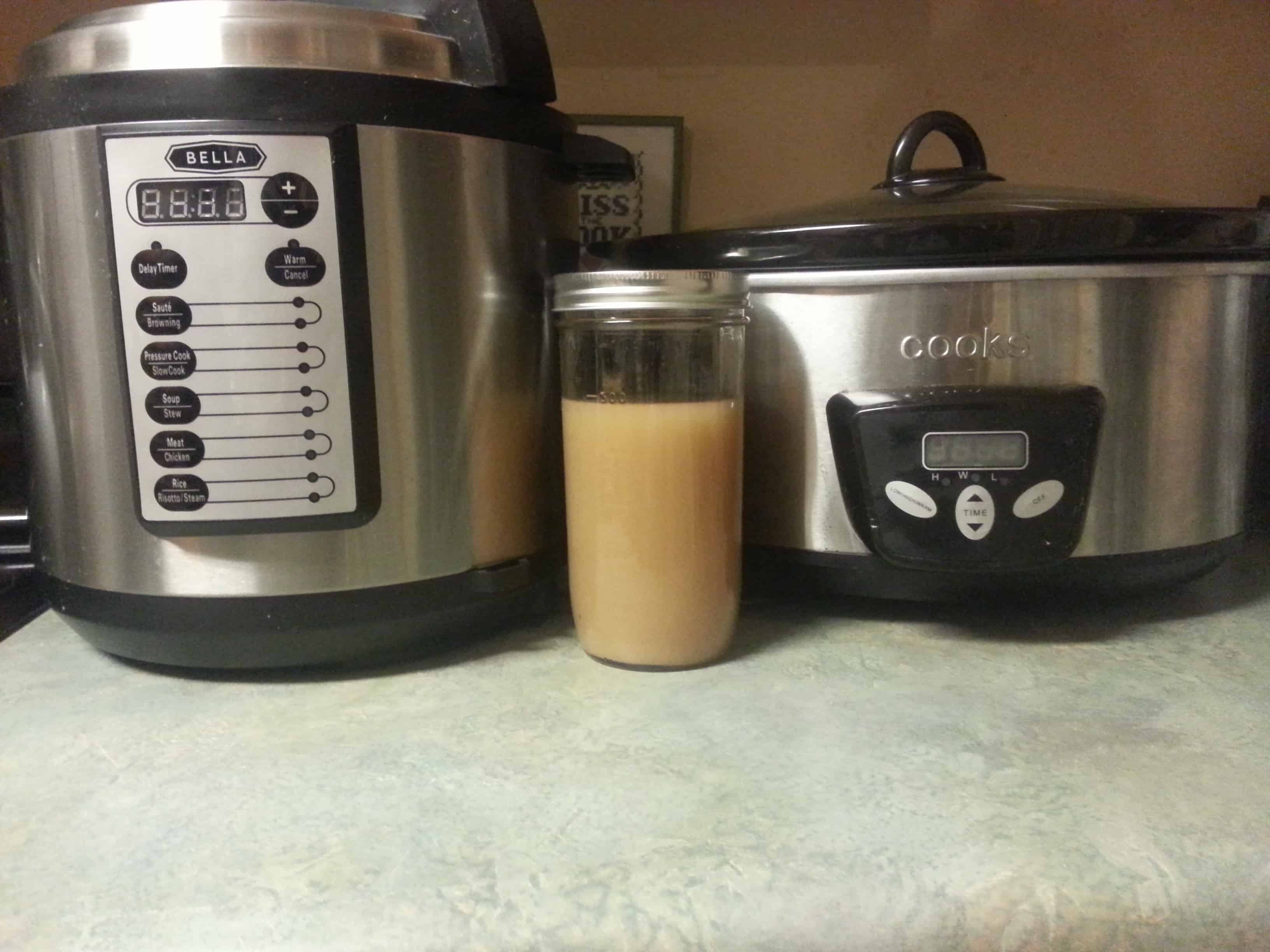 a jar of bone broth next to a pressure cooker and a crock pot