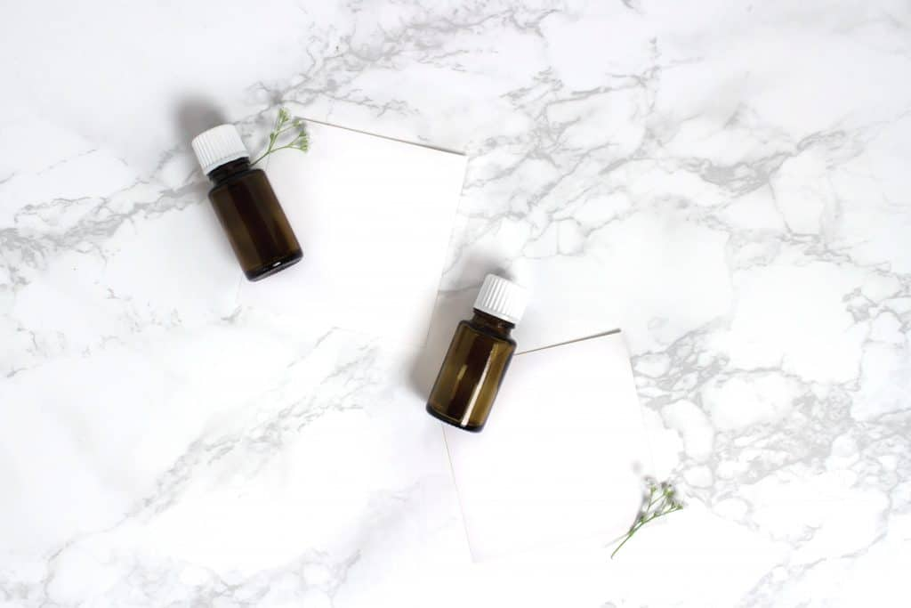two bottles of detoxifying essential oils on a white marble background