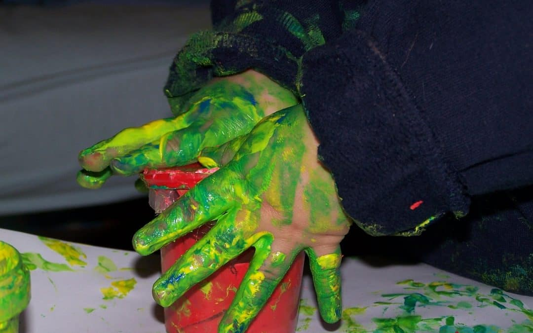 baby playing with green and yellow non toxic finger paints